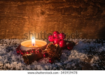 Rustic christmas background with  burning tealight candle,cinnamon, pine cone and cranberries on a wooden table covered with snow. Use it for a  greeting card. Selected focus, narrow depth of field. - stock photo