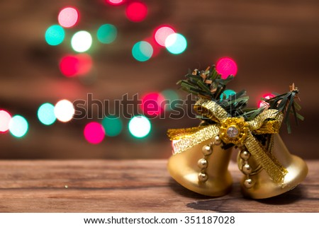 Rustic christmas bells on wooden surface, Blurred christmas lights - stock photo