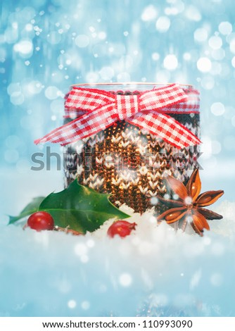 Rustic Christmas still life with a container decorated with a cheerful checked red and white bow with holly and spice nestled in fresh snow - stock photo