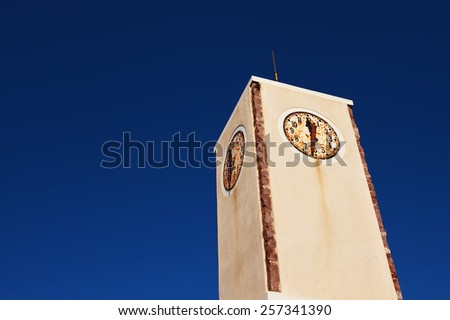 Rustic clock tower in the Village of Oia. Santorini, Greece. - stock photo