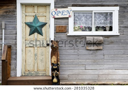 Rustic country store with open sign and star decor on the door. - stock photo