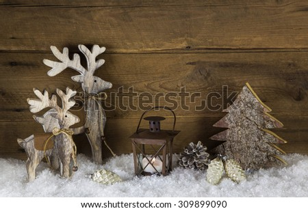 Rustic country style decoration with reindeer, lantern and snow on old wooden background. - stock photo