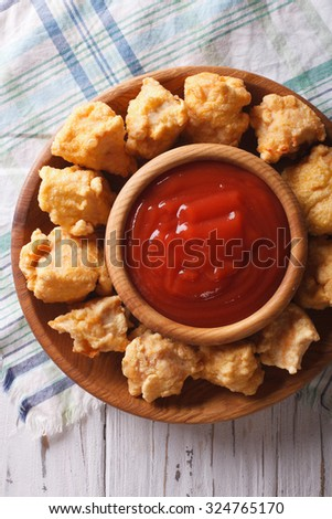 rustic crispy popcorn chicken fillet with sauce close-up on a plate vertical top view - stock photo