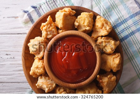 rustic crispy popcorn chicken fillet with sauce on a plate horizontal view from above close-up - stock photo