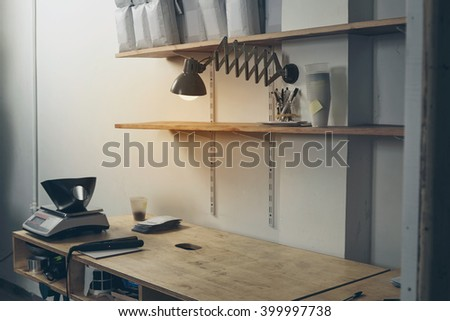 Rustic desktop in professional artisan roastery with empty wooden table handle sealing machine on it ready to work White packages on shelves above table, old vintage lamp with warm light, film effect