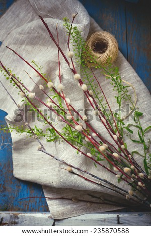 Rustic Easter setting with willow branches, green leaves and twine, on old wooden table. Toned photo. - stock photo