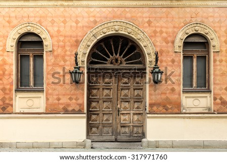 Rustic facade of a building. Double wooden door and windows with arcs.  - stock photo