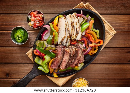 rustic fajita skillet meal with steak and chicken - stock photo