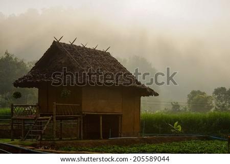 Rustic Farmhouse in the morning haze. - stock photo