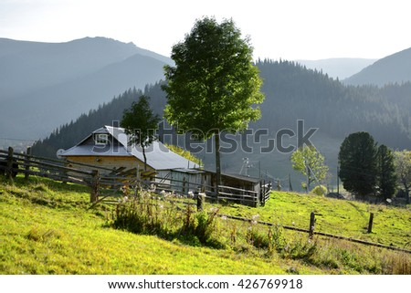 Rustic farmstead in the mountains. Sunny day - stock photo