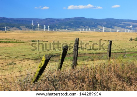 Rustic fence with a wind farm in the background, Washington, USA. - stock photo