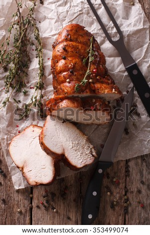 rustic food: roasted turkey breast close-up on a paper on the table. vertical top view - stock photo