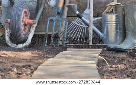 rustic gardening tools on the soil with a wooden path  - stock photo