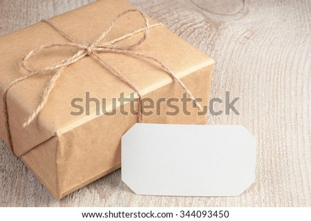 Rustic gift box packed into brown paper tied by twine with blank white card on old white wooden table with space for text - stock photo