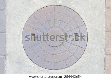 Rustic grunge storm drain manhole cover in city - stock photo