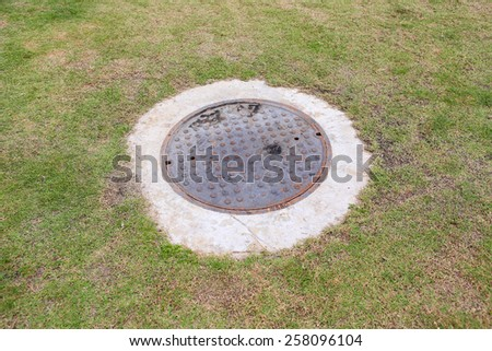 Rustic grunge storm drain manhole cover with green grass background in the garden - stock photo