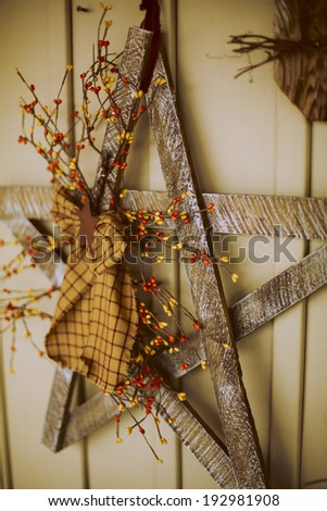 Rustic hand made Christmas star decoration hanging on wall - stock photo