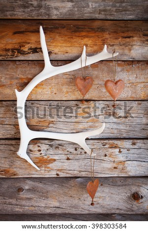 Rustic hearts hanging from white reindeer antler - stock photo