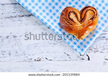 Rustic home-made heart shape freshly backed cinnamon roll on blue checkered cloth over white painted board or table. Above view - stock photo