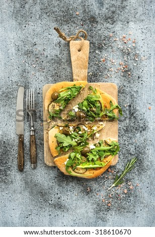 Rustic homemade pizza with eggplant, cheese, olives and arugula on rustic wooden serving board over grunge backdrop. Top view - stock photo