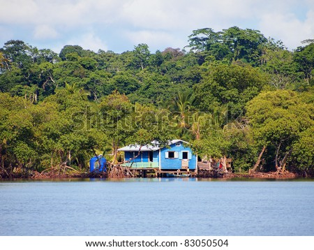 Rustic house on stilts over the sea in the Caribbean coast, with mangrove trees and jungle in background, archipelago of Bocas del Toro, Panama - stock photo