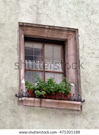 rustic house window with flower box and lace curtain