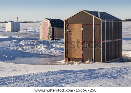 Rustic ice fishing shacks out on the ice.