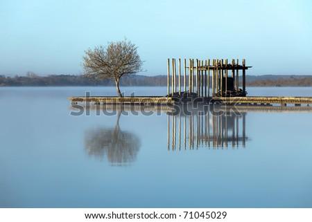 Rustic jetty on a zen-like idyllic lake in Aquitaine, France - stock photo