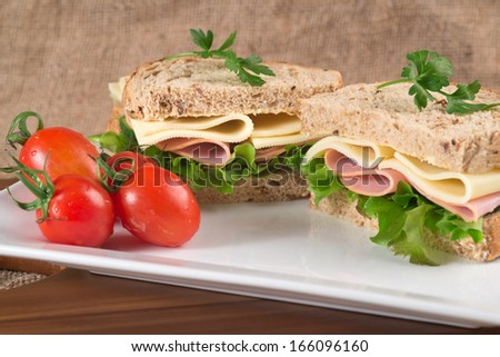 Rustic kitchen setting for fresh ham and cheese sandwich - stock photo