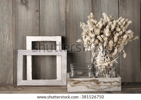 Rustic kitchen still life: dried flowers bunch and wood fotoframes against vintage wooden background.  - stock photo