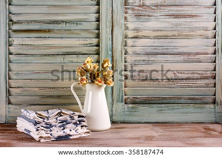 Rustic kitchen still life: white jug with roses bunch and towels stack against vintage wooden shutters.  - stock photo