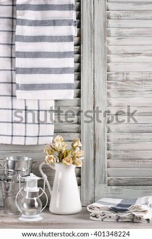 Rustic kitchen still life: white jug with roses bunch, galvanized buckets, lantern and linen towels against vintage wooden shutters. - stock photo