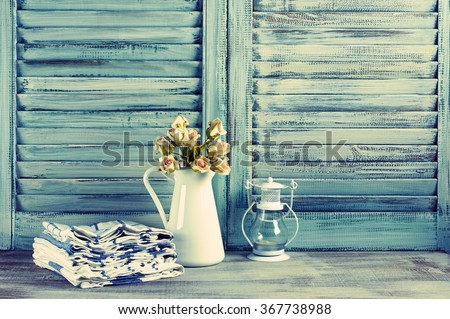 Rustic kitchen still life: white jug with roses bunch, towels stack and lantern against vintage wooden shutters. Filtered toned image. - stock photo