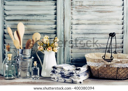 Rustic kitchen still life: wire basket, galvanized buckets with wooden spoons, jug with roses bunch, towels stack and glass bottles against vintage wooden shutters. Filtered toned image. - stock photo