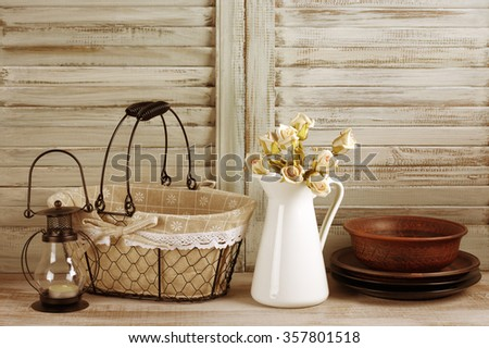 Rustic kitchen still life: wire basket, jug with roses bunch, ceramic dishware and lantern against vintage wooden shutters. Filtered toned image.