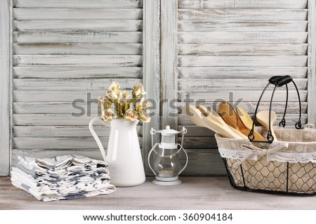 Rustic kitchen still life: wire basket with wooden spoons, jug with roses bunch, towels stack and lantern against vintage wooden shutters.  - stock photo