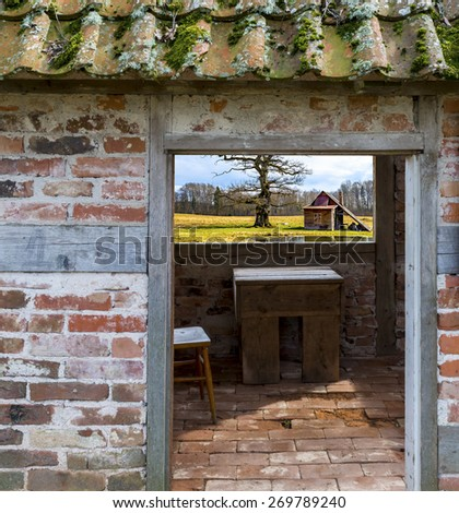 Rustic landscape with old oak and bath house seen through window of old abandoned building  - stock photo
