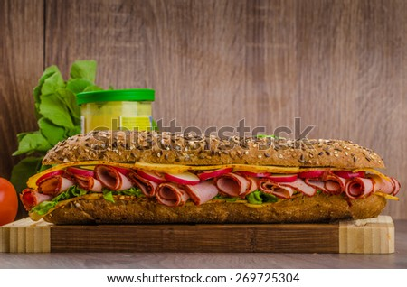 Rustic lined wholemeal baguette with smoked rump, spicy cheese and vegetables - stock photo
