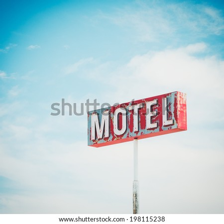 Rustic motel sign against a blue sky - stock photo