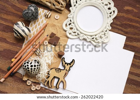 Rustic nature composition with baby deer placed over shredded paper next to pencils and artistic white photo frame with buttons over brown and white placeholder paper on the right and vintage wood - stock photo