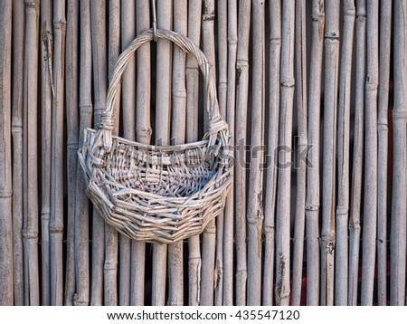 Rustic objects.  Old wicker basket on bamboo fence. Empty. - stock photo
