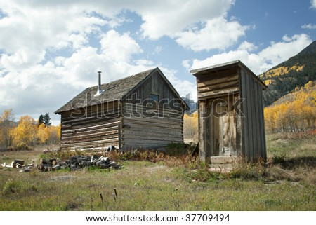 Rustic old house and outhouse in Autumn season in Colorado at Ashcroft Ghost Town - stock photo