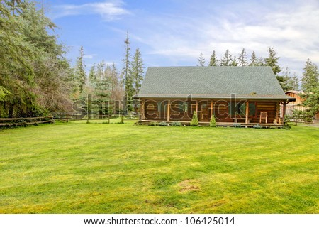 Rustic old log cabin exterior with large grass lawn.