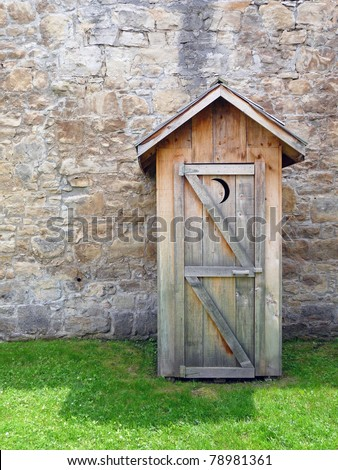 Rustic outhouse with vintage stone wall - stock photo