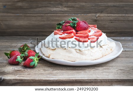 Rustic Pavlova cake with fresh strawberries and whipped cream over a rough wood background. Front view - stock photo