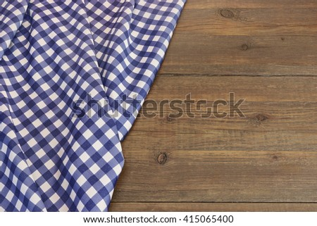 Rustic Picnic Wooden Table With Blue Folded Checkered Tablecloth, Top View, Copy Space - stock photo