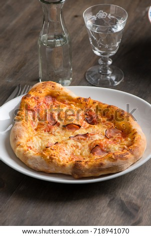 Rustic pizza with ham on wood table