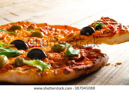 Rustic pizza with salami, olives and fresh herbs lifted slice