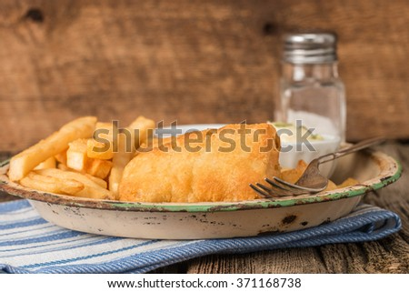 Rustic plate of traditional fish and chips. - stock photo