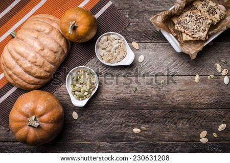 Rustic pumpkins with cookies and seeds on wood. Autumn Season food photo - stock photo